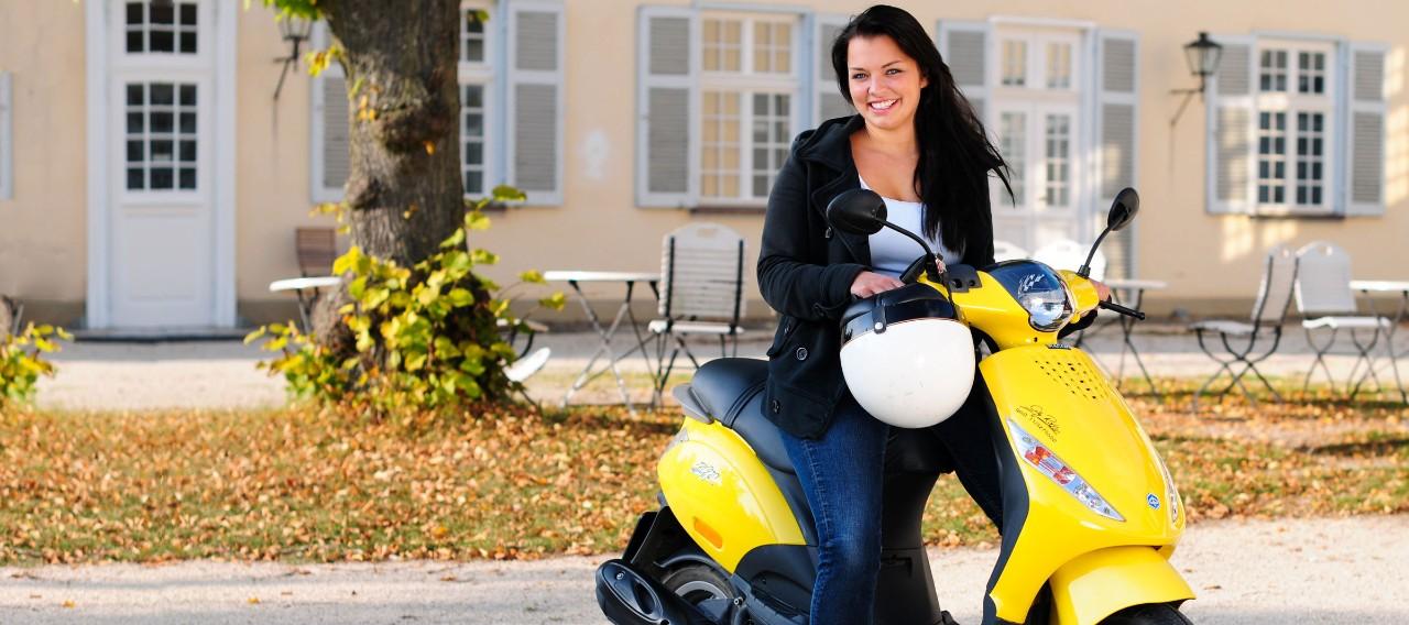 Junge Frau auf Motorroller