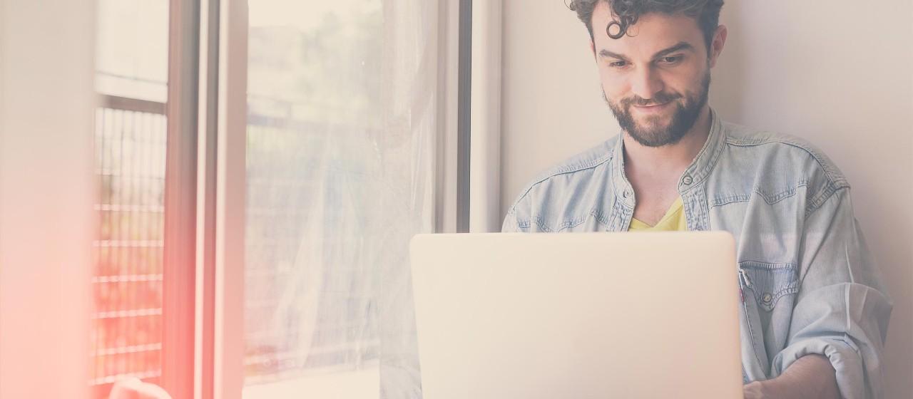 Junger Mann mit Laptop
